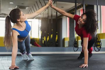 Two multiracial fitness girls doing push ups