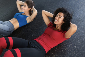 Young fit women at the gym doing abs workout