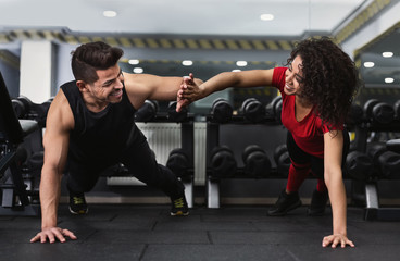Couple giving high five while doing push ups