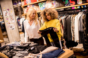 Two pretty young women choosing clothes from new collection in department store