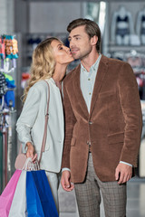 young woman holding shopping bags and kissing man in boutique