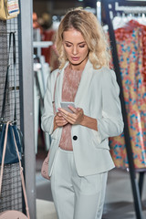 beautiful young woman using smartphone while shopping in fashion store