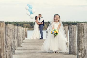 kleines Blumenmädchen bei der Hochzeit am See