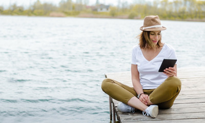 Pretty girl reading e-book outdoors by the lake
