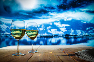 Two glasses with white wine on an old wooden table in a Christmas mood