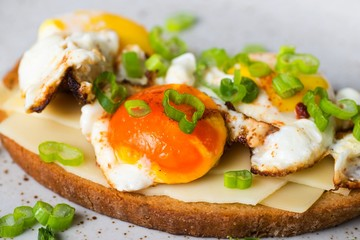Toasts with fried eggs,cheese and onion shoots.