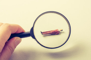 Tiny figurine of man model  under magnifying glass