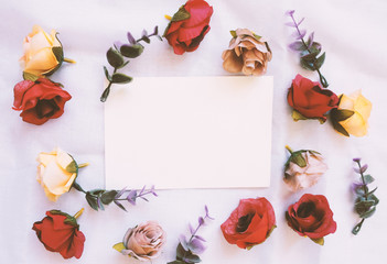 Flat lay style of blank card with flowers decorated on white cloth, top view