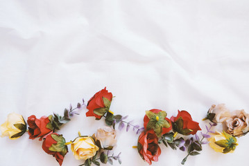 Flat lay style of copy space with flowers decorated on white cloth, top view