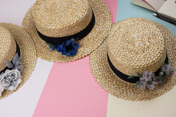 Straw boater hat with silk flowers on a bright pink, yellow and white background
