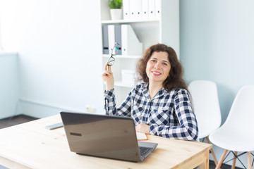 Coworking, graphic designer and business people concept - woman is working at the office with laptop