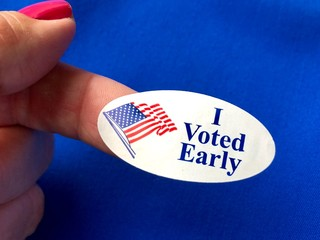 I voted sticker on a woman's finger with blue background