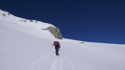 several backcountry skiers hike and climb to a remote moutain peak in Switzerland on a beautiful winter day