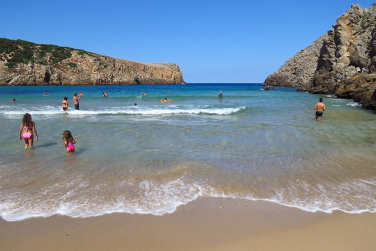 Swimming and having fun at Cala Domestica, a beach surrounded by high cliffs in the northwest of Sardinia, Italy