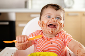 Smiling baby with messy face eating chocolate dessert with spoon