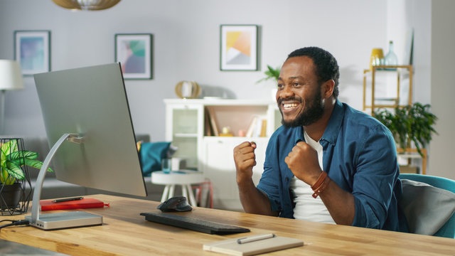 """Excited Young Man Uses Personal Computer at Home, Wins Big, Does """"Yes"""" Gesture, Celebrates Victory Emotionally. In the Background Cozy Living Room."""