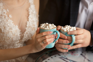 Wedding in cold weather. Bride and groom holding cups of coffee with marshmallow in cafe Wall mural