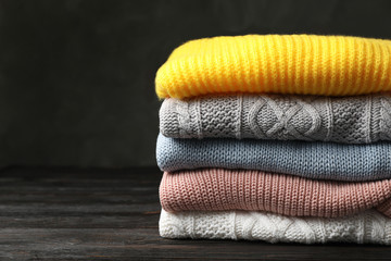 Fototapete - Stack of folded knitted sweaters on table. Space for text
