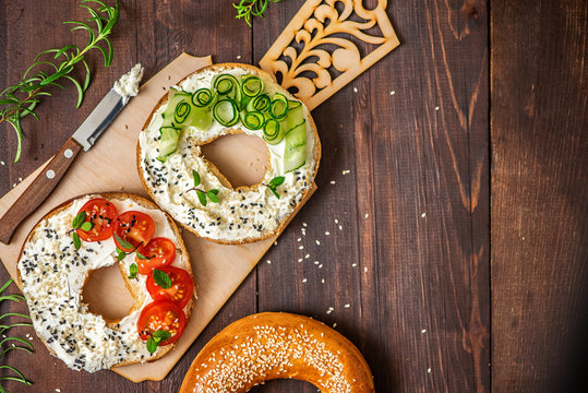 Bagels with cream cheese, sesame, tomato and cucumber on a wooden Board. Top view flat lay. With copy space
