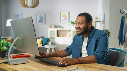Handsome African Amertican Man Works on a Personal Computer while Sitting at the Desk of His Cozy Living Room.