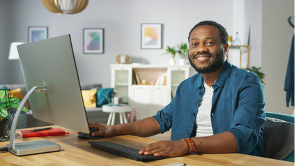 Smiling Young Man Uses Personal Computer, Nods in Agreement and Smiles Charmingly Looking at the Camera. In the Background Cozy Living Room.