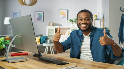 Portrait of the Handsome Black Man Works on a Personal Computer, Has Success and Shows Thumbs Up with Both Hands. In the Background Cozy Living Room.