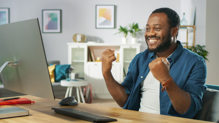 """Happy Young Man Uses Personal Computer at Home, Wins Big, Does """"Yes"""" Gesture, Celebrates Victory Emotionally. In the Background Cozy Living Room."""
