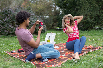 Beautiful young couple taking pictures with a camera of each other outside on a picnic blanket