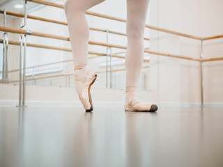 Close up legs in pointe. Training before performance. Woman practicing in classical ballet in tutu dress in gym or ballet hall. Performing sensual dance
