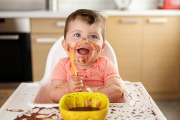 Messy happy baby eating chocolate dessert with spoon