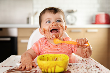 Happy baby eating chocolate dessert with spoon