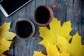 Yellow maple leaves, two brown cups of black tea or coffee and mobile phone on brown wooden background.