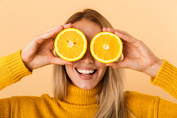Beautiful woman covering eyes with citrus lemons posing isolated over yellow wall background. Fototapete