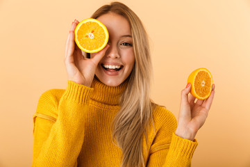 Fototapeta Beautiful woman covering eyes with citrus lemons posing isolated over yellow wall background. obraz