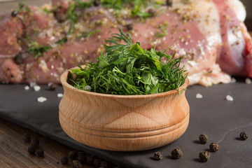 sliced green spices, parsley and dill, in a wooden bowl, against the background of raw turkey meat, close-up shot