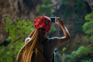 Girl tourist makes photo with phone