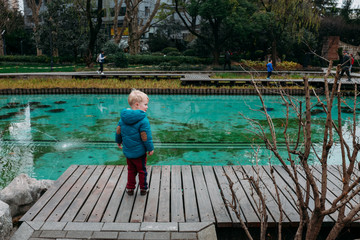 Little boy standing by a park pond