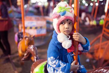 Kid enjoyed joyride in carousel in a fair