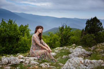 Young happy woman in long dress on the mountainside.