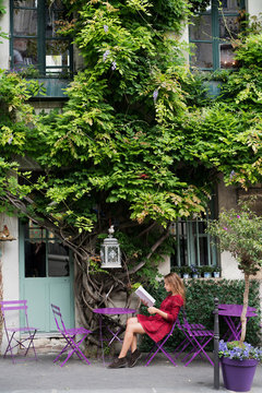 yang women sitting in the open caffe in Paris looking at menu under green tree holds and reading menu