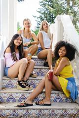 Portrait of female friends sitting on stairs in a summer day.