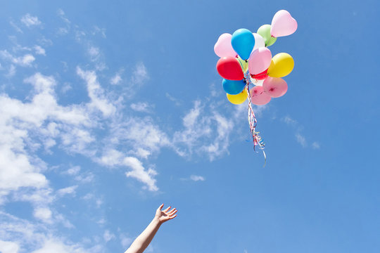 Hand letting balloons fly up in the sky