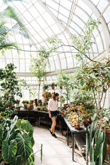 teenage girl looking at beautiful flowers in greenhouse