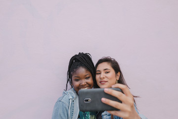 Friends taking selfie together on pink wall