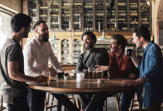 Group of men laughing and drinking beer in bar