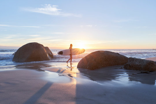 Woman with surfboard walking on beach during sunset
