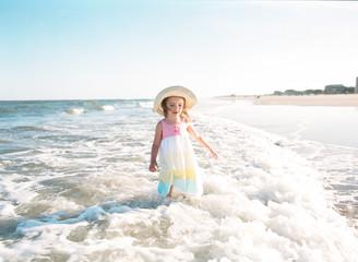little girl standing in ocean on beach