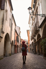 Woman in red walking on the streets of Padova