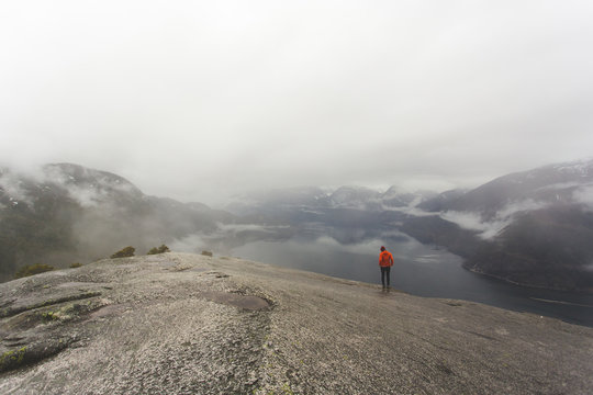 A young woman standing on top of The Chief in Squamish BC on a cloudy day