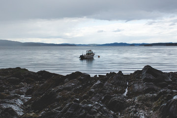 A small fishing boat moored beside a rocky point before a storm